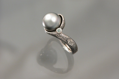 MK509 - custom 14k white gold sterling silver mokume gane ring. Center is 11mm tahitian pearl with green diamond accent.