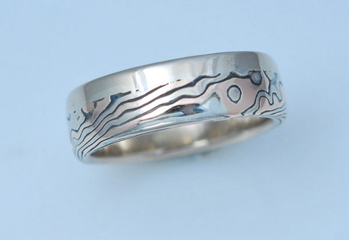Customized tri color mokume band with wide solid side.  Very unique