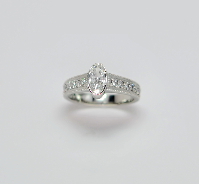 14kt white gold with .75ct oval diamond with .50cttw diamonds.